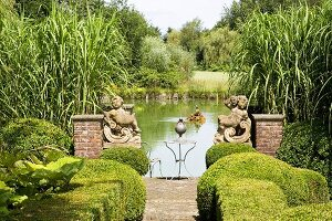 Path lined with box hedges and flanked by angel statues leading to lake