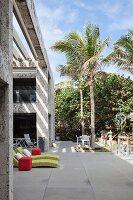Liegen und Sitzplätze auf moderner Terrasse unter Palmen