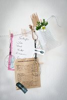 Hand-made wire utensils and shopping list clipped to cord with clothes pegs decorating kitchen wall