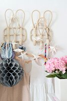 Summer dresses hung from coathangers on coat pegs decorated with fairy lights