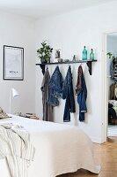 Clothes hooks below black wall-mounted shelf in bedroom