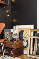 Picture frames and stacked vintage suitcases against black wall