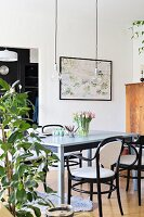 Spring flowers on pale grey wooden table and black bentwood chairs