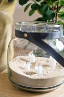 Sand and white candles in glass jar