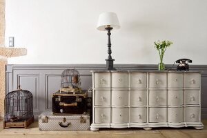 Table lamp on vintage chest of drawers, stacked trunks and birdcages in living room