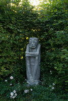 Stone guardian figure in a niche of the hornbeams hedge