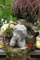 Stone cherub in small larch wreath next to heather