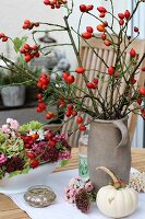 Branches of rose hips in stoneware jar next to autumnal flowers