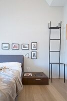 Delicate metal chair used as dressing stand next to bed