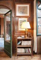 Bücherregal mit Tischleuchte vor einer verktäfelten Wand im Flur
