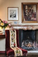 Old chair with tapestry and red velvet cover in front of fireplace