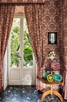 Three-tiered table against patterned wallpaper and matching curtains