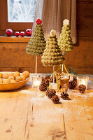 Tiny crocheted Christmas trees and tealight holders on wooden table