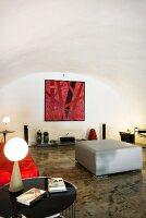 Designer-Wohnbereich mit restaurierter, weißer Gewölbedecke und glänzendem Betonboden