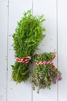 Bunches of fresh tarragon and thyme tied with striped twine