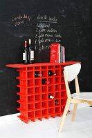 Rotes Weinregal vor einer Wand mit Tafelfarbe mit notiertem Rezept