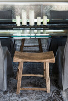 Rustic wooden stool at elegant glass table with arrangement of candles