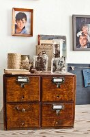 Reels of twine and glass vessels on top of vintage chest of drawers