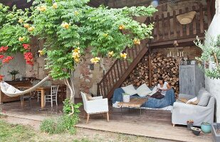 Woman sitting on comfortable country-house terrace with firewood stacked against wall