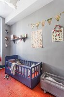 Vintage cot below bunting and posters on grey wall