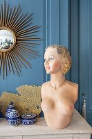 Retro bust of woman, ceramic pots and fan coral on mantelpiece below sunburst mirror on wall