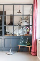 Standard lamp next to demijohn bottles on small retro table against dove-grey partition wall with glass panels