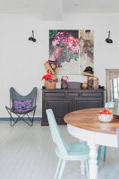 Butterfly Chair, sideboard and floral artwork in retro interior