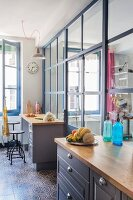 Kitchen base units with wooden worksurface against glass partition