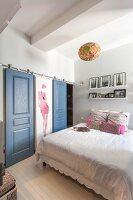 Wardrobes in niche with dove-grey sliding doors in feminine bedroom