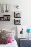 Black and white photos on sideboard in feminine bedroom