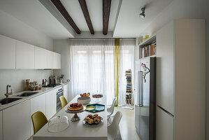 Verschiendene Stühle am Esstisch in der modernen weißen Küche