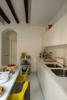 Gelbe Stühle am Esstisch in der modernen weißen Küche