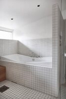 Bathtub in white-tiled bathroom with glass door screening shower