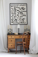 Candelabras and table lamp on old wooden desk below artwork on wall