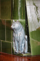 Green tiled stove with cat ornament