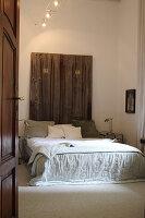 Disused wooden doors used as headboard of double bed in bedroom