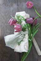Linen napkin tied with rosemary sprig, name on ribbon and snake's head fritillary