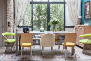 Various chairs around dining table in front of glass wall looking into garden