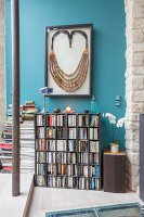 Large framed necklace above bookcase on blue wall