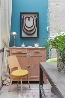 Large framed necklace above old cabinet on blue wall