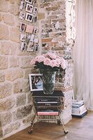 Vase of roses on old trolley against exposed stone wall