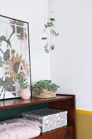 Blätter- und Tannenzweige in Glaskugeln über Retro-Sideboard aufgehängt