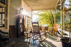 Wooden rocking chairs on sunny veranda