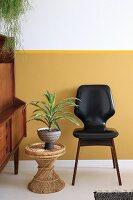 Yucca on wicker stool next to black retro chair