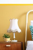 Old table lamp and succulent planted in cup on bedside cabinet