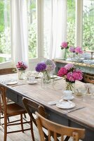 Set table with several vases of hydrangeas in conservatory