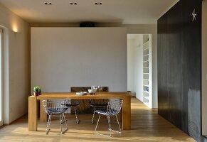Massiver Esstisch und Metallstühlen vor weißer Wandscheibe, Durchgang und schwarze Metallverkleidung