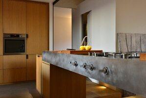 Metall-Küchentheke mit Gasherd und Einbauschrankwand neben Durchgang