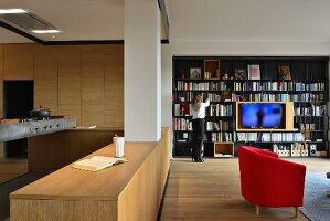Offenes Wohnen mit moderner Holzküche und schwarzem Metall-Bücherregal mit integiertem Fernseher