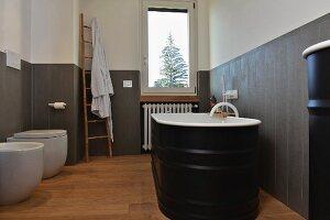 Schwarze freistehende Badewanne vor grauer Wandverkleidung